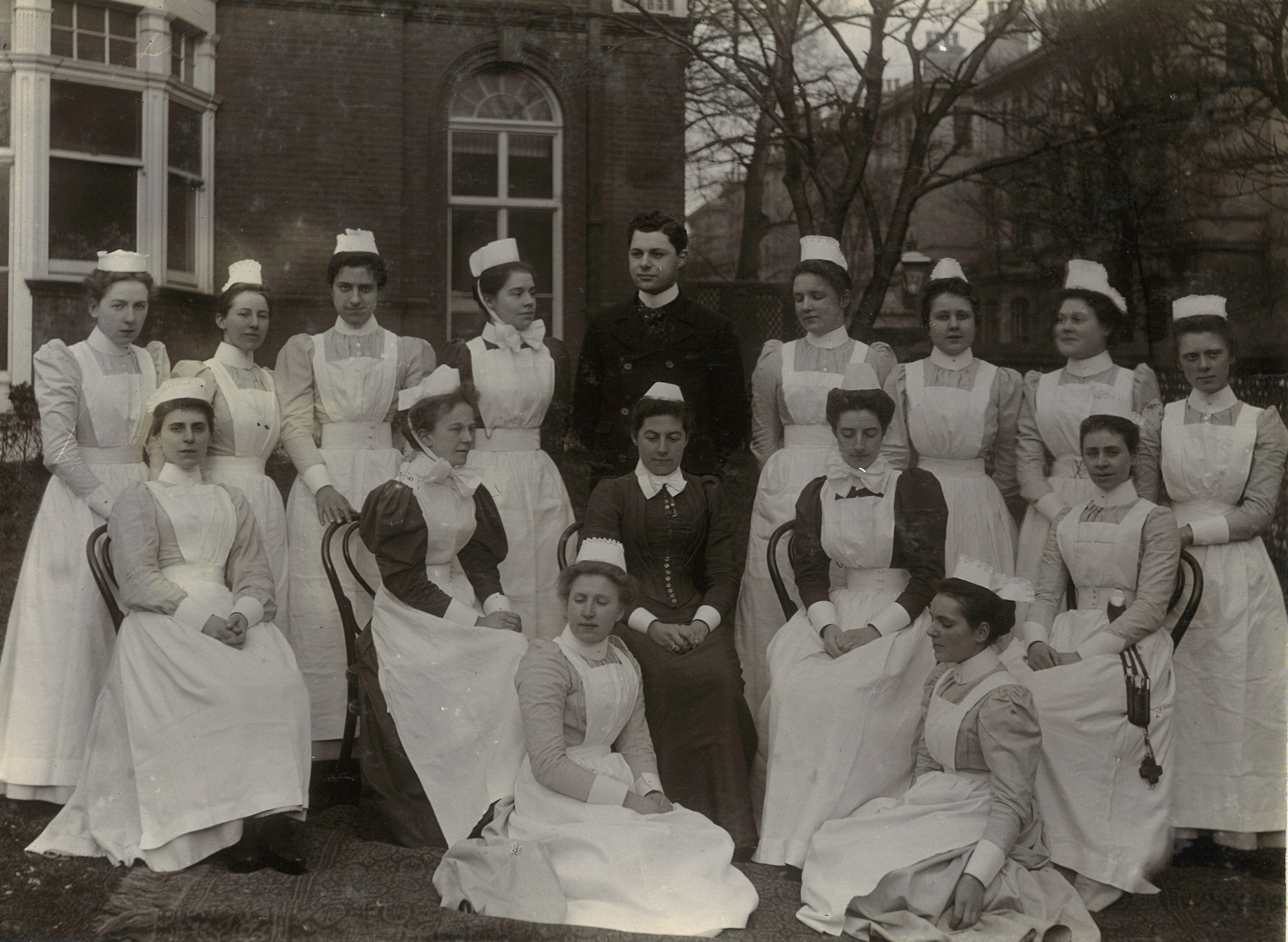 A large group of hospital staff in uniforms posing in the grounds of the hospital, c. 1900