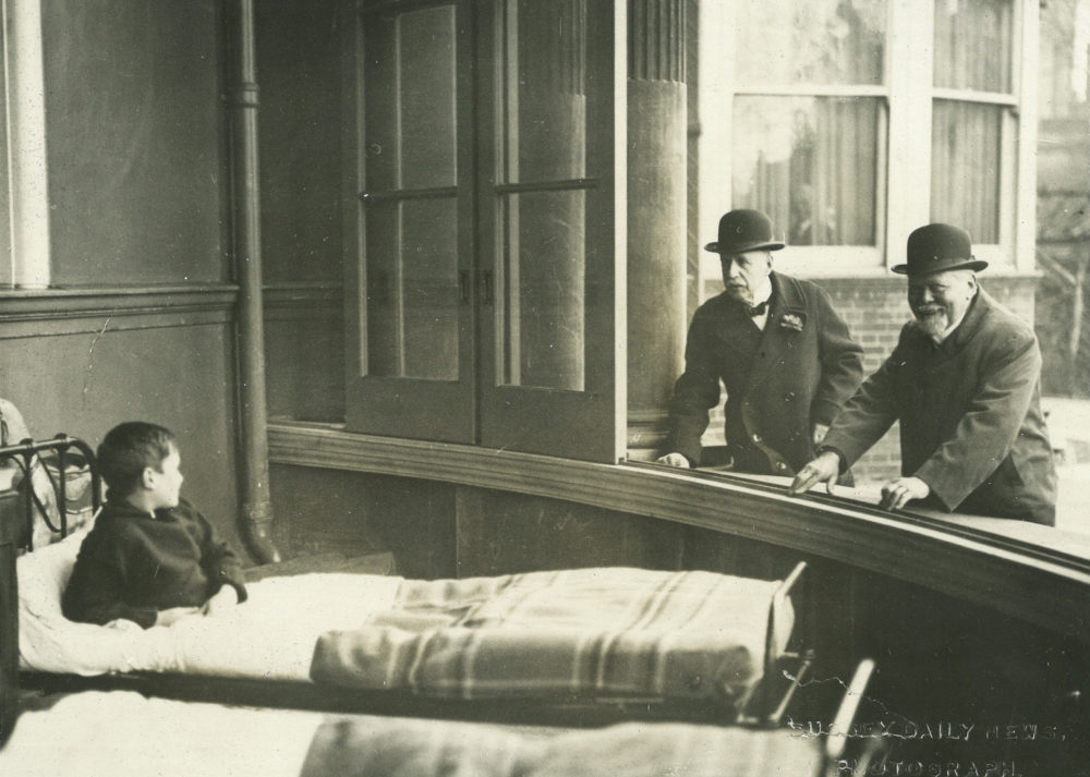 Young patient having a chat with two older gents through the open windows of Royal Alexandra Hospital, c. 1900.