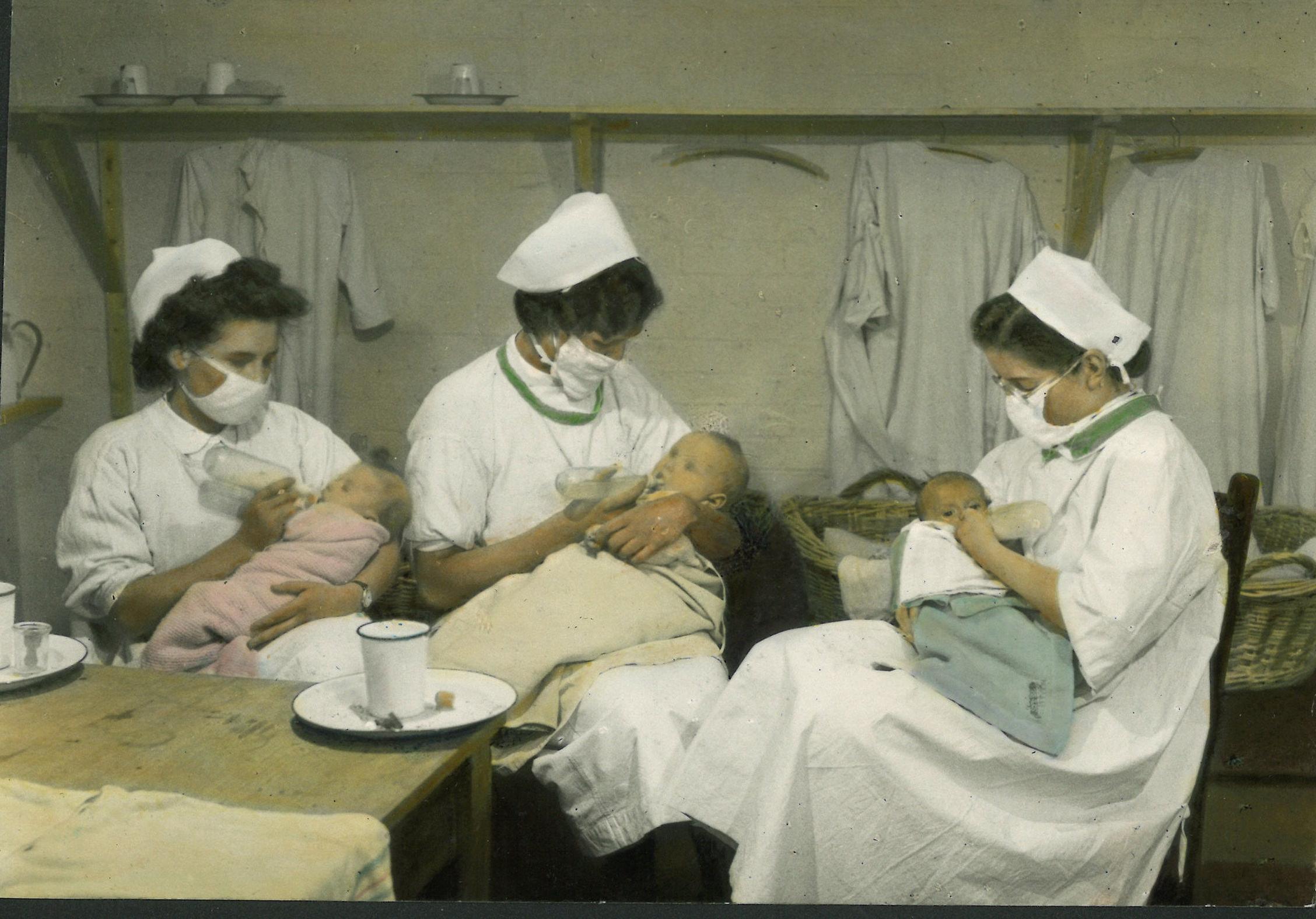 Nurses bottle-feeding infants, 1940s