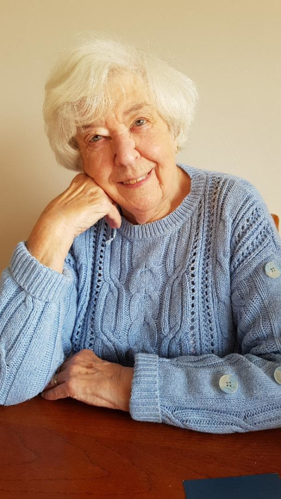 Photo of Betty Field wearing a blue knit cardigan, head resting lightly on hand.