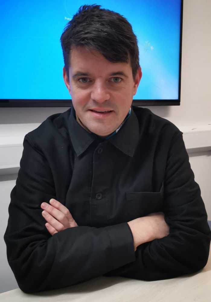 Photo of Daniel Locke sitting with arms crossed wearing a long-sleeved black shirt.