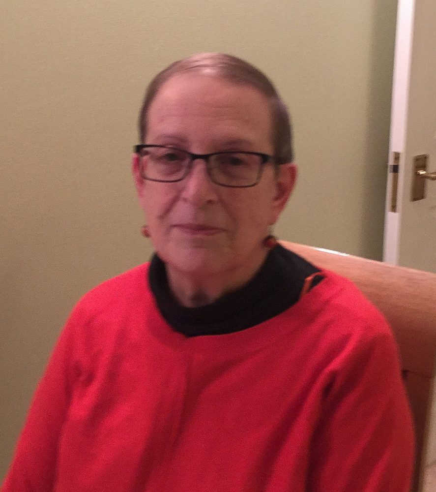 Photo of Helen Brownstone wearing a bright red jumper and glasses.