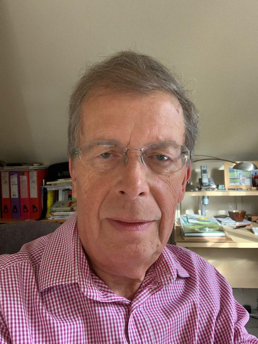 Photo of John Hartley wearing dark pink and white small check shirt.