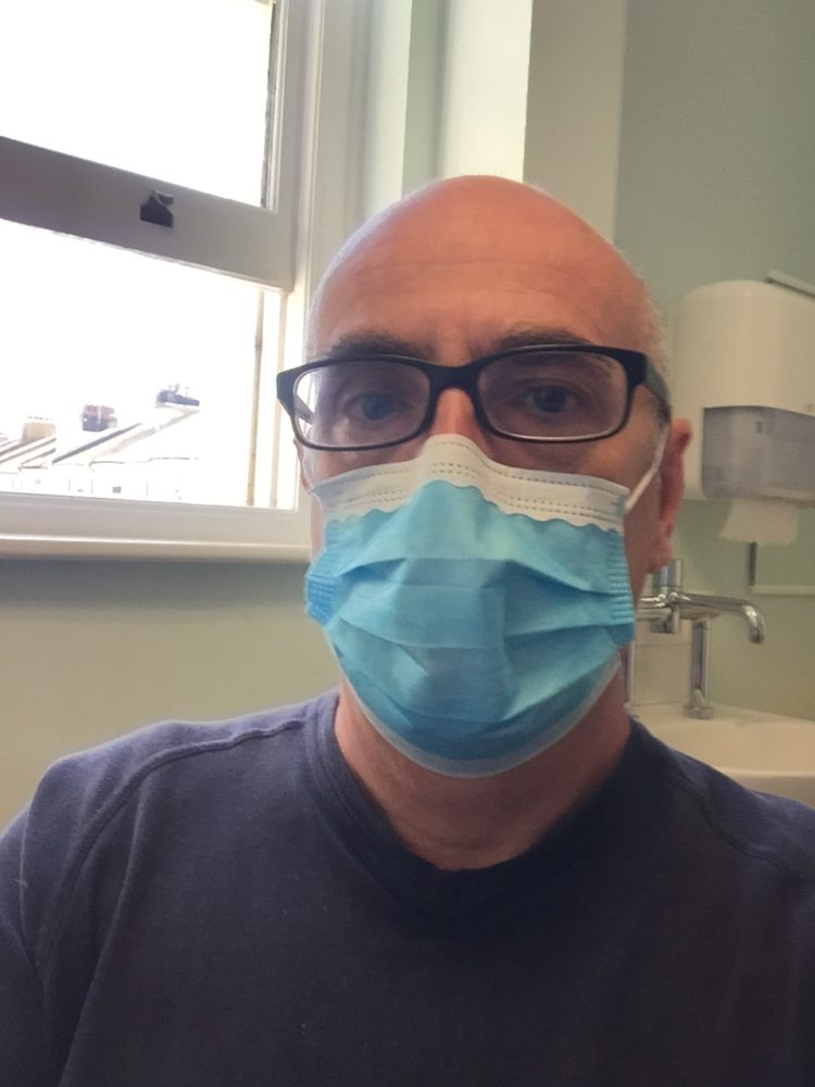 Photo of John Quin wearing blue surgical mask.